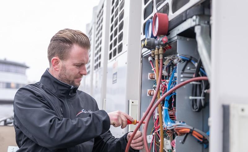 Een monteur verhelpt een airconditioningstoring